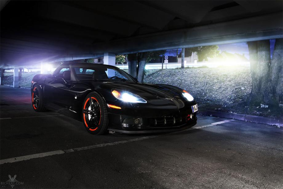 Nachts fahren Autos an der Corvette vorbei, ihre Lichter ziehen Streifen im Bild. Die Scheinwerfer der Corvette sind eingeschaltet.