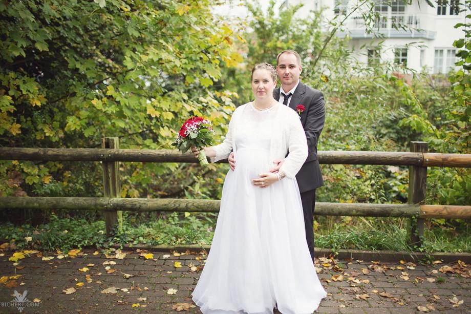 Bräutigam umarmt seine frisch vermählte schwangere Braut im Park vor dem Standesamt.