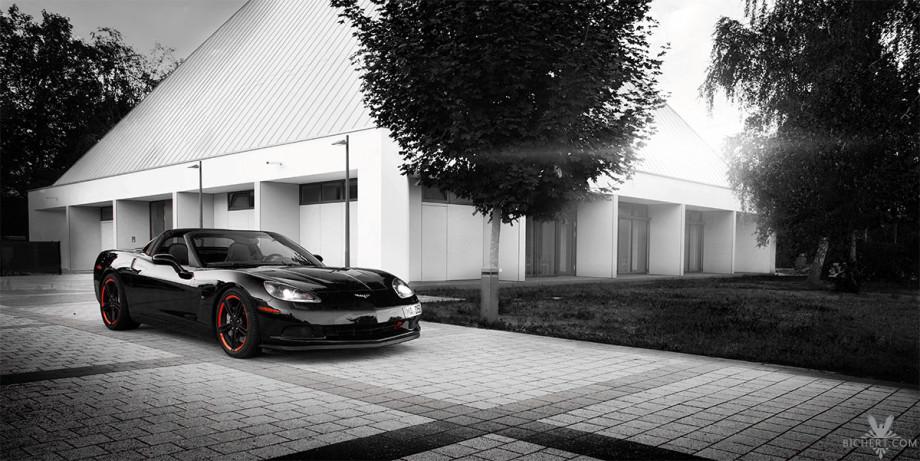 Corvette C6 schwarz-weiss Bild fotografiert auf dem Grundstück einer Gemeinde.