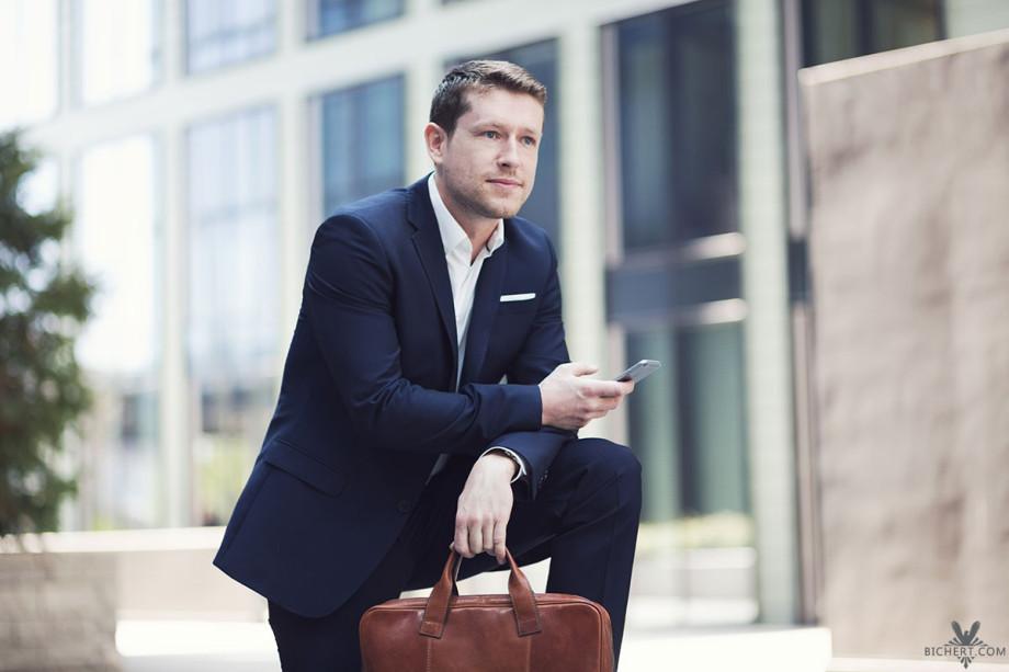 Business Portrait mit Handy und Tasche in der Hand