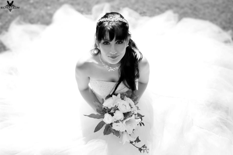 Die Braut mit Brautstrauß in der Hand posiert beim Hochzeitsshooting im Rosengarten