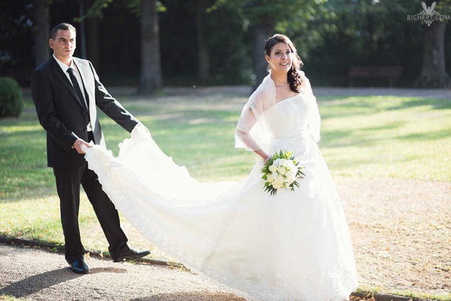 Braut geht spazieren und der Braeutigam traegt ihre Schleppe