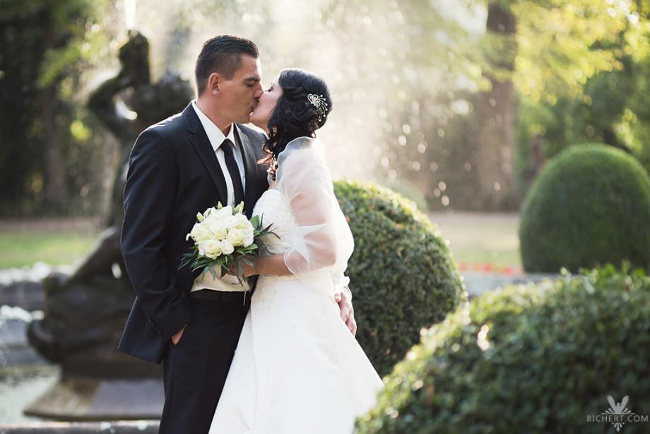Hochzeitsfoto vom Brautpaar, das sich vor einem lichtdurchfluteten Brunnen in der Parkanlage am Standesamt Hoechst, kuesst.