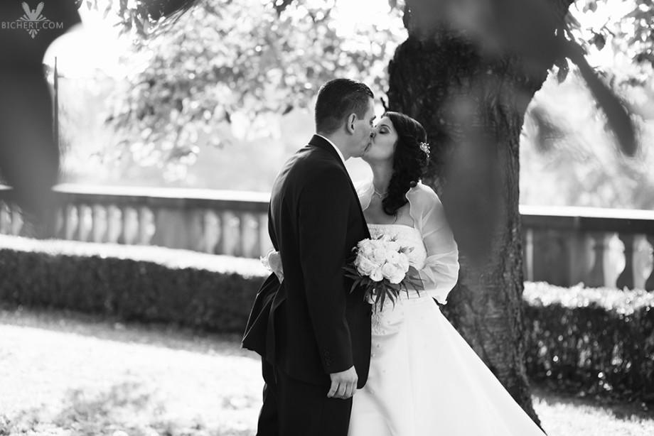 Brautpaar küsst sich unter der Baumkrone im Park des Bolongaro Palastes