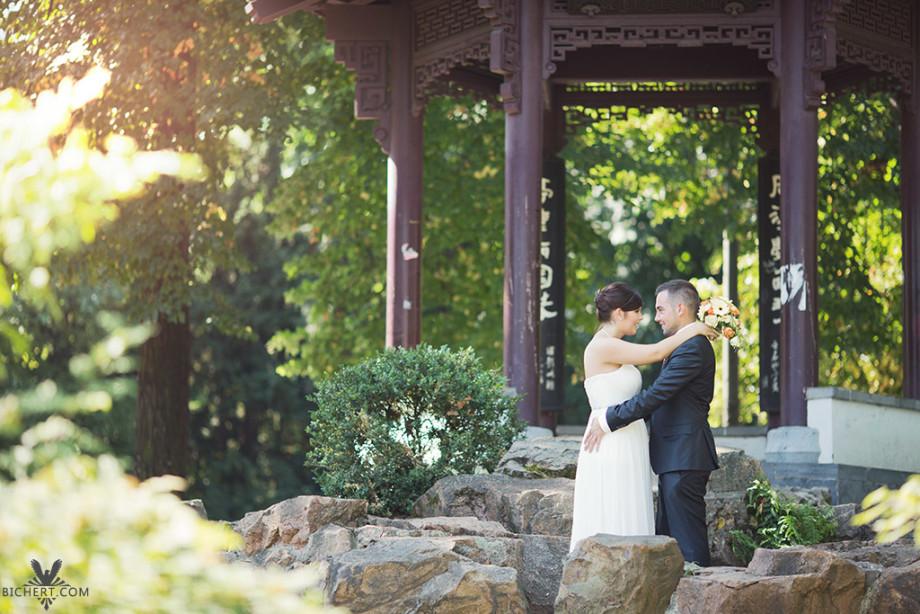 Das Brautpaar steht im Park, umarmt sich, während der Hochzeitsfotograf die Bilder macht
