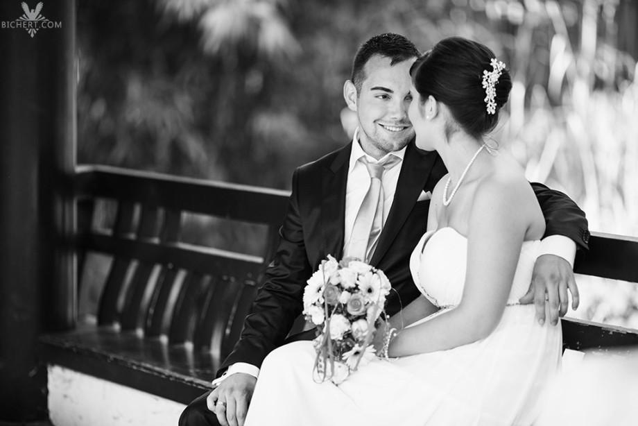 Braut und Bräutigam sitzen auf der Bank im Park, das Bild wurde in schwarzweiss aufgenommen
