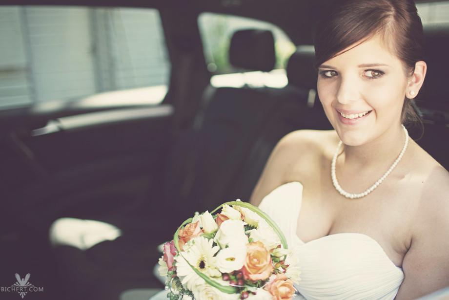 Brautportrait während die Braut im Hochzeitsauto sitzt