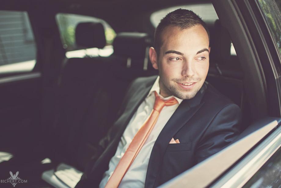 Bräutigam sitzt hinten im Hochzeitsauto